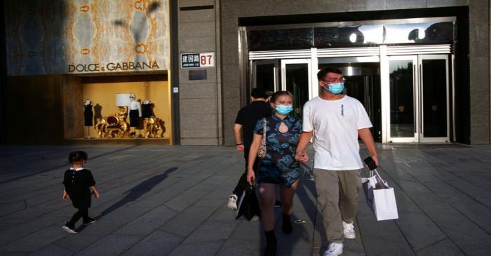 FILE PHOTO: People wearing face masks following the COVID-19 outbreak walk out of a shopping