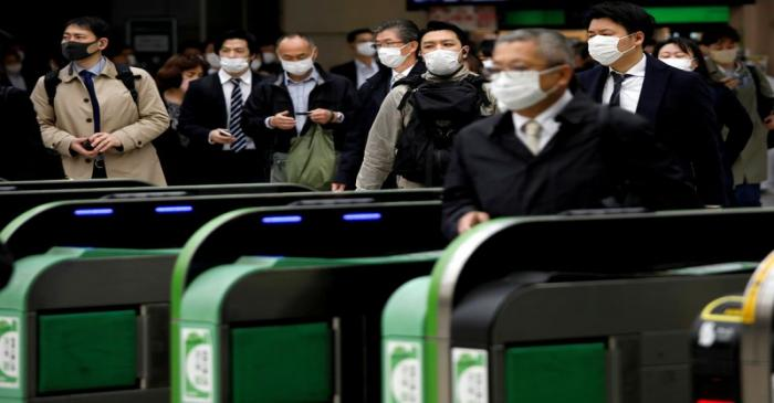FILE PHOTO: Passengers wearing protective face masks, following an outbreak of the coronavirus