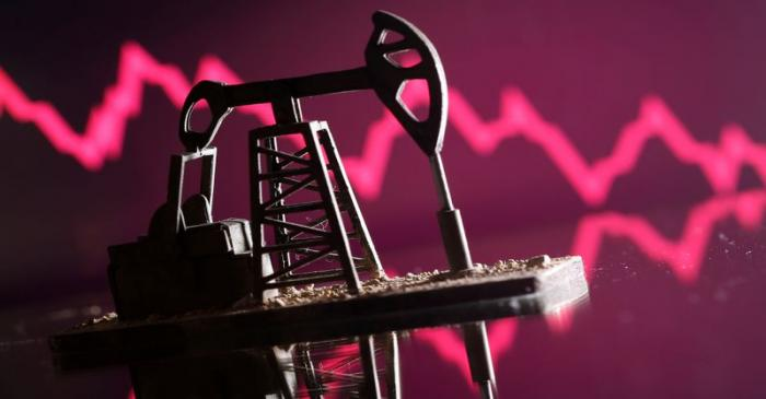 A 3D printed oil pump jack is seen in front of displayed stock graph in this illustration