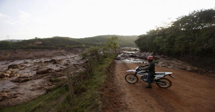 FILE PHOTO: A man observes a road blocked with mud after a dam owned by Vale SA and BHP