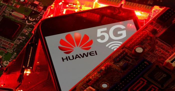 FILE PHOTO: A smartphone with the Huawei and 5G network logo is seen on a PC motherboard in