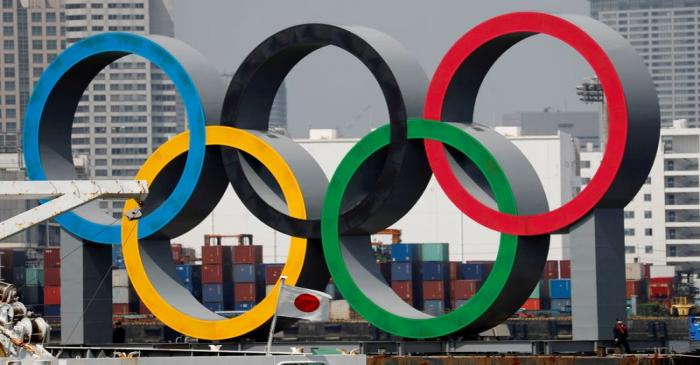 FILE PHOTO: The giant Olympic rings are seen behind Japan's national flag at the waterfront