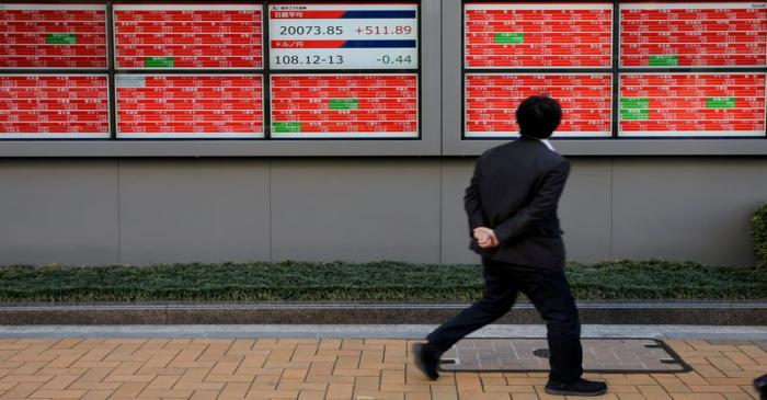 A man looks at an electronic board showing the Nikkei stock index outside a brokerage in Tokyo