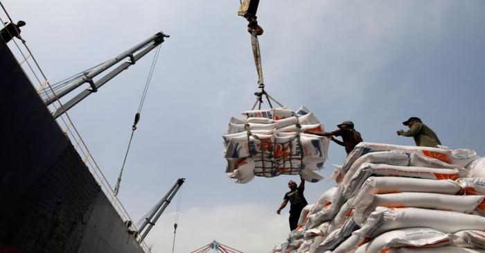 FILE PHOTO: Workers unload bags of rice from a cargo ship onto a truck at Tanjung Priok Port in