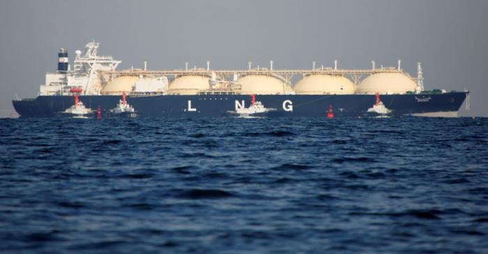 A LNG tanker is tugged towards a thermal power station in Futtsu