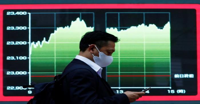 A man wearing a protective face mask walks past a screen displaying a graph showing recent
