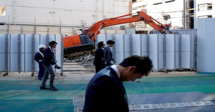 FILE PHOTO: Businessmen walk past heavy machinery at a construction site in Tokyo's business