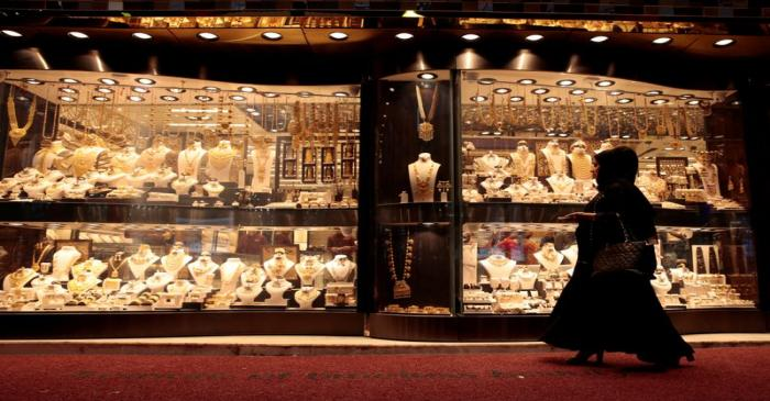 FILE PHOTO: A woman walks past gold jewellery displayed in a shop window at the Gold Souq in