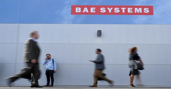 Trade visitors walk past an advertisement for BAE Systems at Farnborough International Airshow