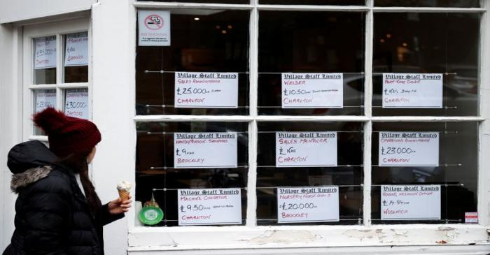 A person looks at adverts in the window of a job agency in London