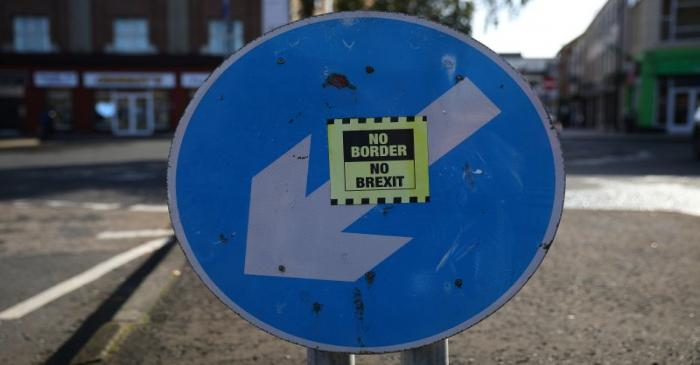 A 'No hard Border' poster is seen below a road sign on the Irish side of the border between