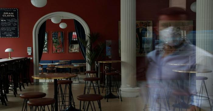 A man wearing a protective mask is reflected on the window of a closed vermouth bar, amid the