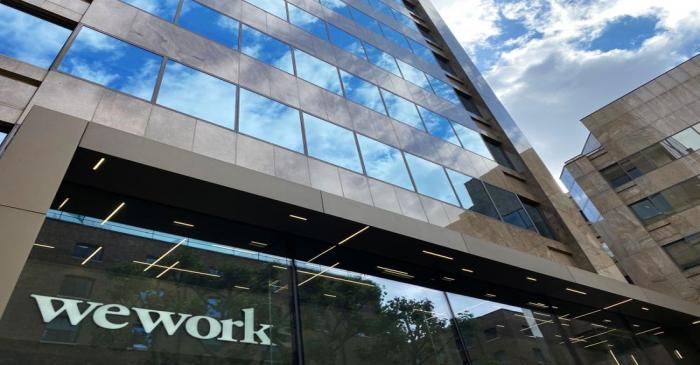 The logo of WeWork is seen in the window of a building in London