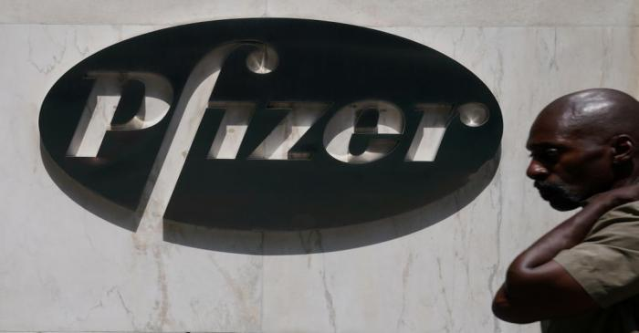 FILE PHOTO: A man walks past a sign outside Pfizer Headquarters in the Manhattan borough of New