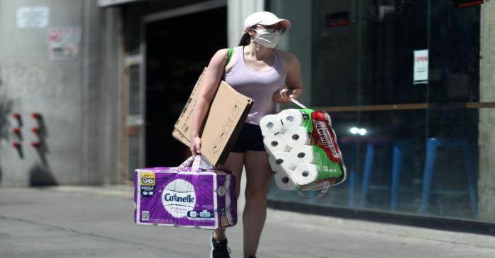 A woman carries toilet paper down the street on the first day of the reopening of some