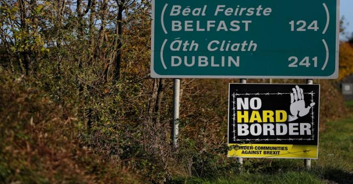 FILE PHOTO: A 'No hard Border' poster is seen below a road sign on the Irish side of the border