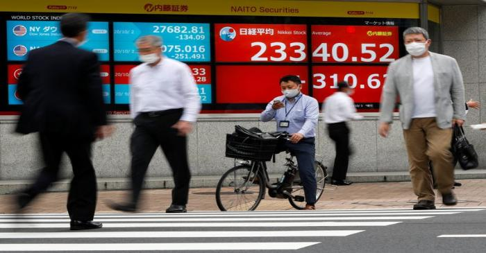 Passersby wearing protective face masks walk past a screen displaying Nikkei share average and