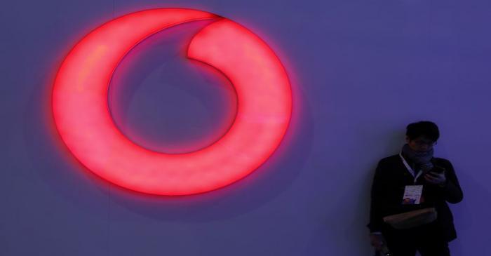A man checks his mobile phone next to a Vodafone logo at the Mobile World Congress in Barcelona