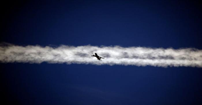 FILE PHOTO: An aeroplane flies underneath the jet stream of another aircraft above the Italian