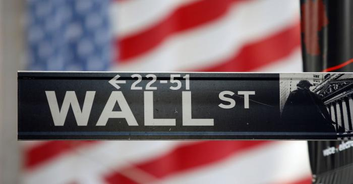 FILE PHOTO: A sign for Wall Street is seen with a giant American flag in the background across