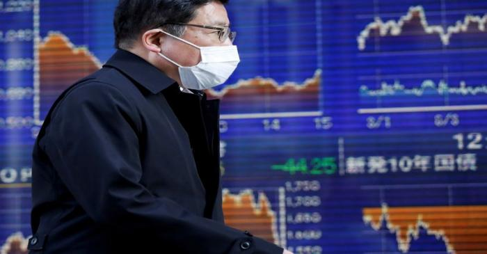 FILE PHOTO: A passerby wearing a protective face mask, following an outbreak of the