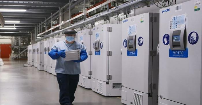 FILE PHOTO: A worker passes a line of freezers holding coronavirus disease (COVID-19) vaccine