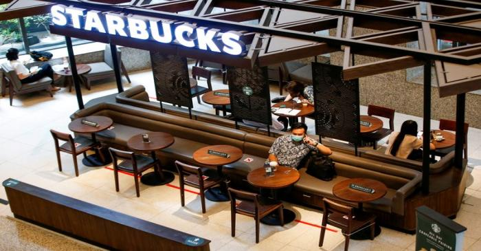 FILE PHOTO: A man wearing a protective mask uses a phone at a Starbucks cafe inside the