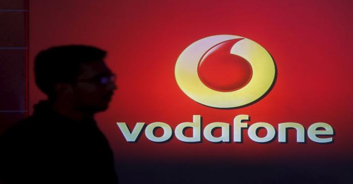 A man casts silhouette onto an electronic screen displaying logo of Vodafone India after a news