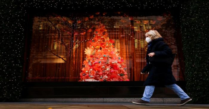 A pedestrian walks past a Christmas tree in a window display at Selfridges department store on