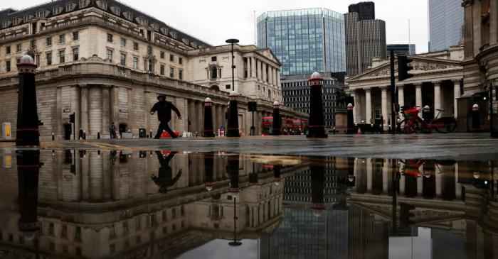The Bank of England and Royal Exchange are reflected in a puddle as a pedestrian walks past in