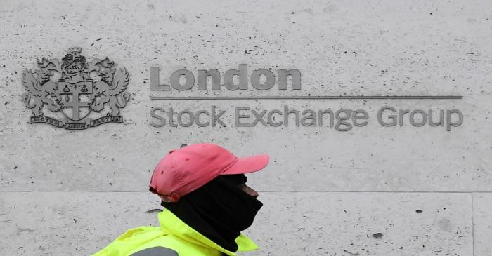 A street cleaning operative walks past the London Stock Exchange Group building in the City of