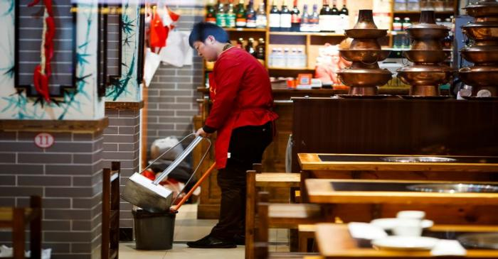 A waiter cleans the floor of a restaurant after closing hours in Beijing