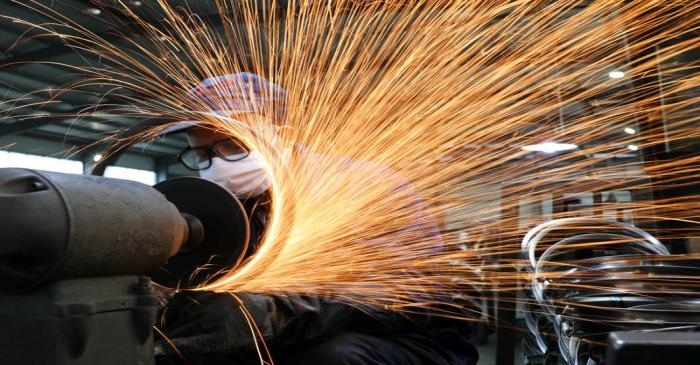 Worker wearing a face mask works on a production line manufacturing bicycle steel rim at a