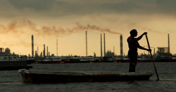FILE PHOTO: A fisherman rows his dinghy past oil refineries near port terminals in Singapore