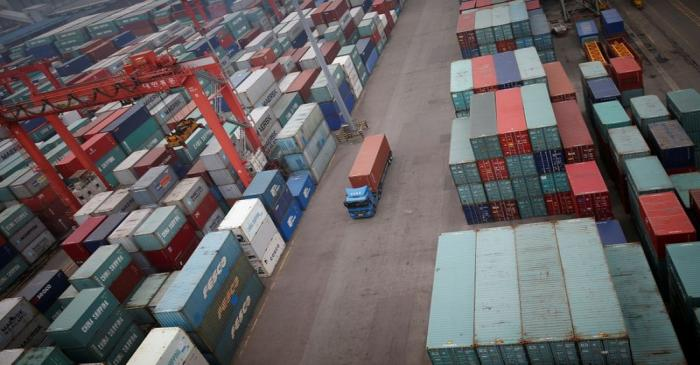 FILE PHOTO: A truck drives between shipping containers at a container terminal at Incheon port