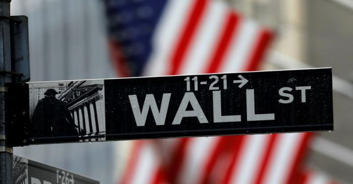 FILE PHOTO: Raindrops hang on a sign for Wall Street outside the New York Stock Exchange in New