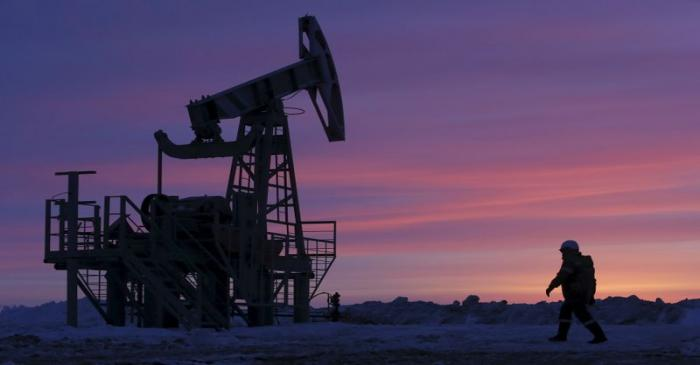 File photo of a worker walking past a pump jack on an oil field owned by Bashneft company near