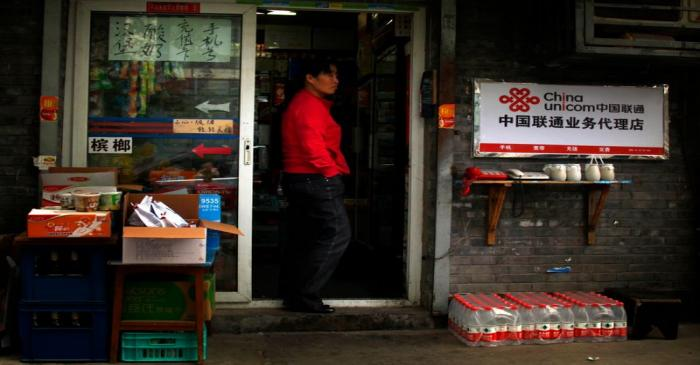 A convenience store owner stands in the doorway of her shop next to a sign advertising China