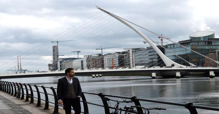 A man walks past offices in the Irish Financial Services Centre in Dublin