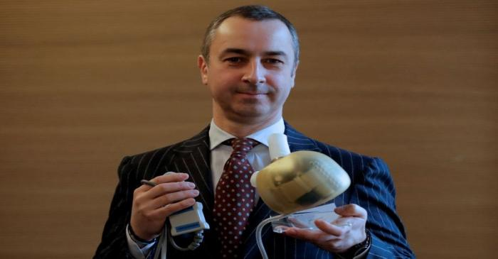 Carmat Chief Executive Officer Stephane Piat holds an artificial heart as he poses after the