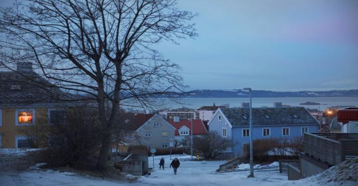 People walk through a residential street in Trondheim