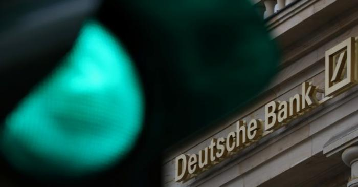 A green traffic light is seen next to the logo of Germany's largest business bank, Deutsche
