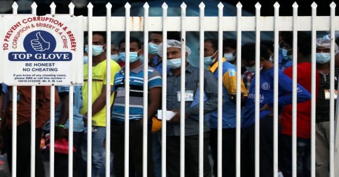 Workers wait in line to leave a Top Glove factory after their shifts in Klang