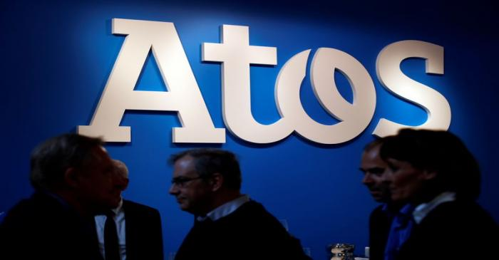 People walk in front of the Atos company's logo during a presentation of the new Bull sequana