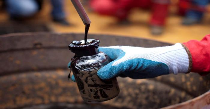 FILE PHOTO: A worker collects a crude oil sample at an oil well operated by Venezuela's state