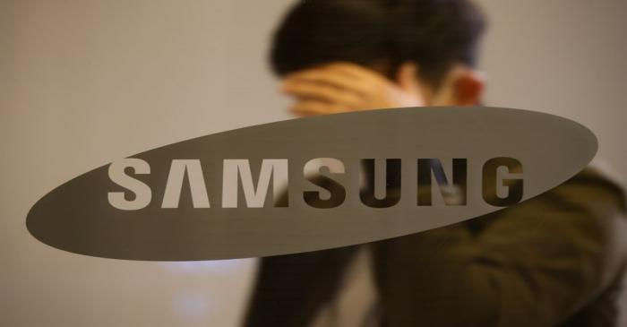 A man walks past the logo of Samsung at its office building in Seoul