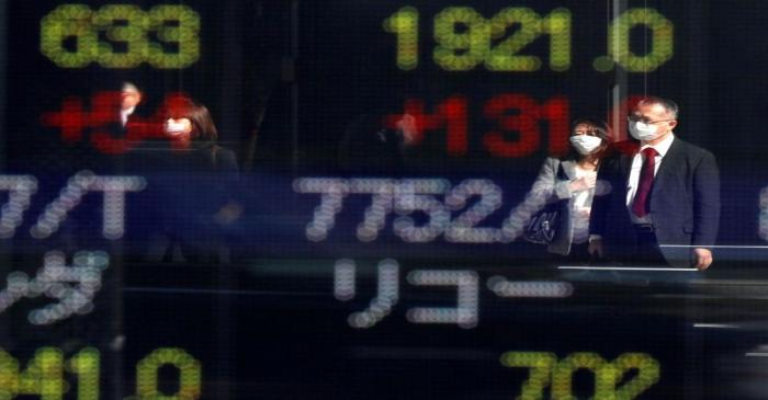 Passersby wearing protective face masks are reflected on a stock quotation board outside a