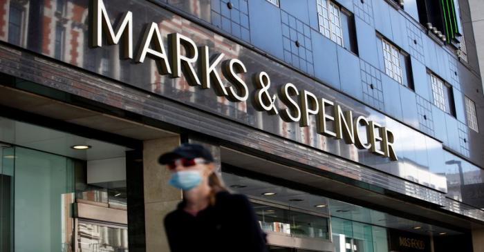 A woman walks past a M&S store at Oxford Street in London