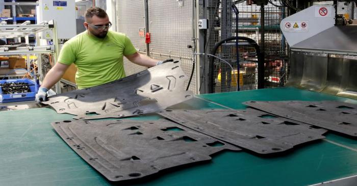 An employee holds an underfloor shield in production at a plant of Swiss car parts supplier
