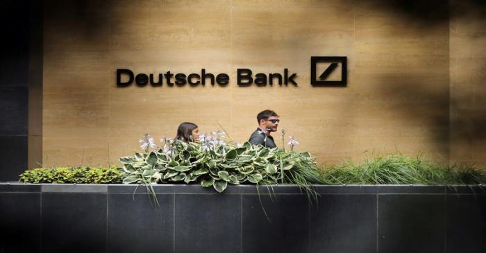 FILE PHOTO: People walk past a Deutsche Bank office in London